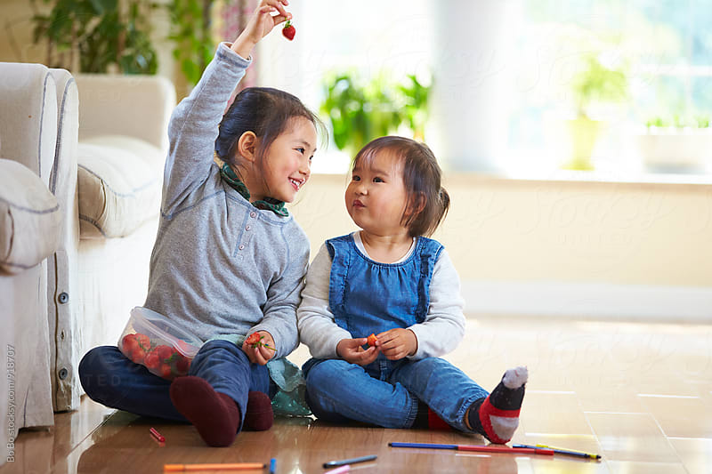 two little asian girls eating strawberry in home by Bo Bo for Stocksy United
