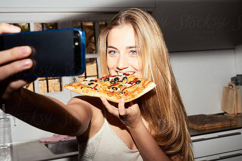 Young blondie taking selfie while eating pizza by Guille Faingold for Stocksy United