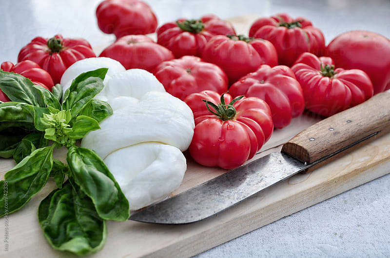 Food: Bulls heart tomatos, mozzarella cheese and basil by Ina Peters for Stocksy United