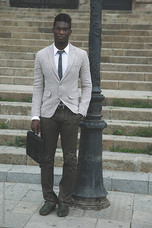 African young businessman with a briefcase standing in front of street stairs by BONNINSTUDIO for Stocksy United