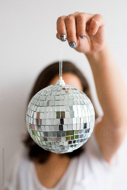 Young woman holding disco ball by Pixel Stories for Stocksy United