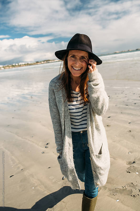 Beautiful young woman walking and playing on the beach wearing gumboots by Jonathan Caramanus for Stocksy United