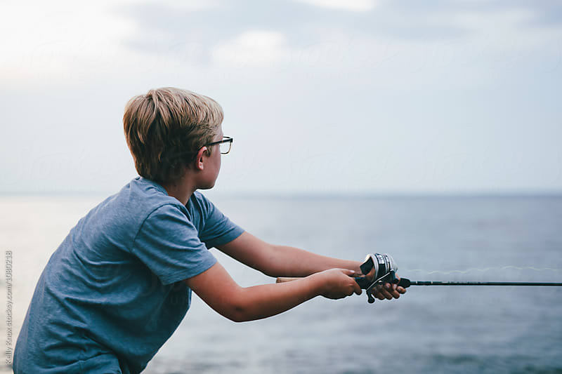 boy casting a fishing pole by Kelly Knox for Stocksy United