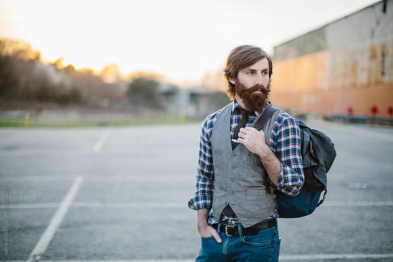 Portrait of a hip and trendy bearded man in a parking lot by Jakob for Stocksy United