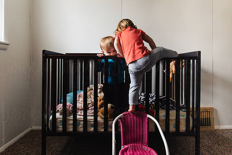 Toddler climbing into crib with sibling by Jessica Byrum for Stocksy United