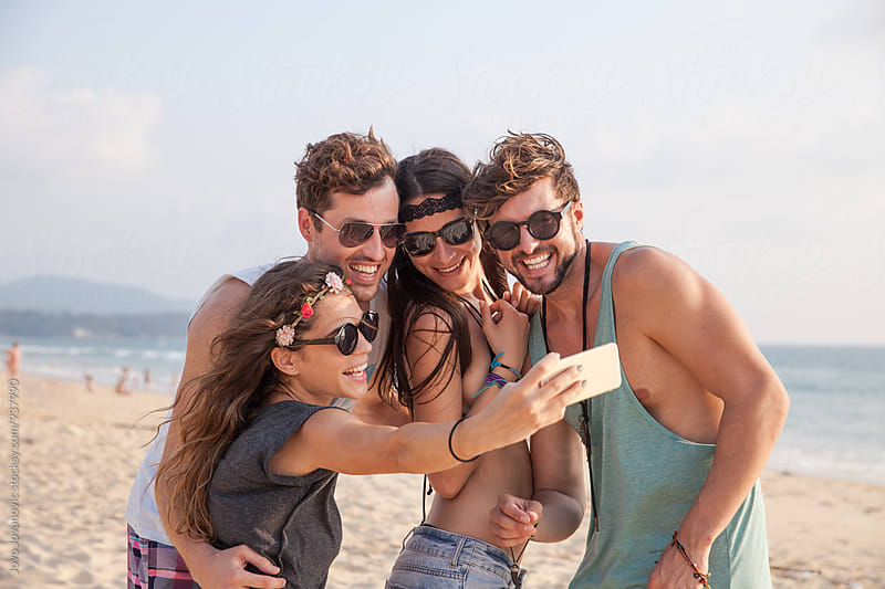Group of friends taking a selfie together on the beach by Jovo Jovanovic for Stocksy United