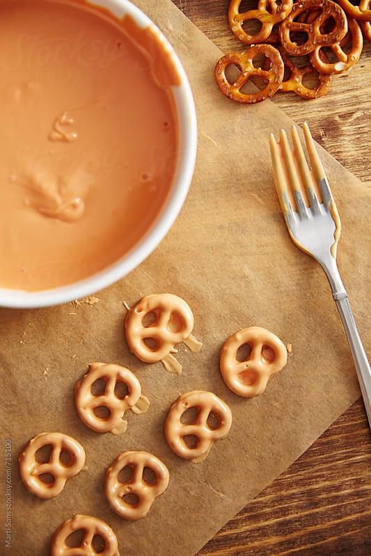 Preparing pumpkin shaped pretzels by Martí Sans for Stocksy United
