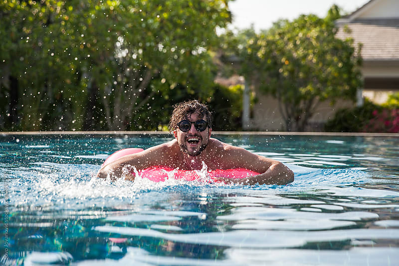 Man laughing while floating in swimming pool by Jovo Jovanovic for Stocksy United