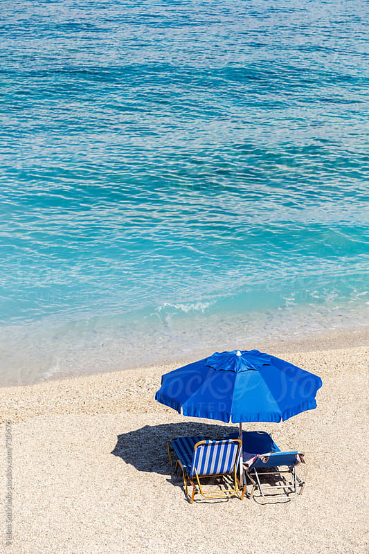 Umbrella and Lounge Chairs on a Beach by Helen Sotiriadis for Stocksy United