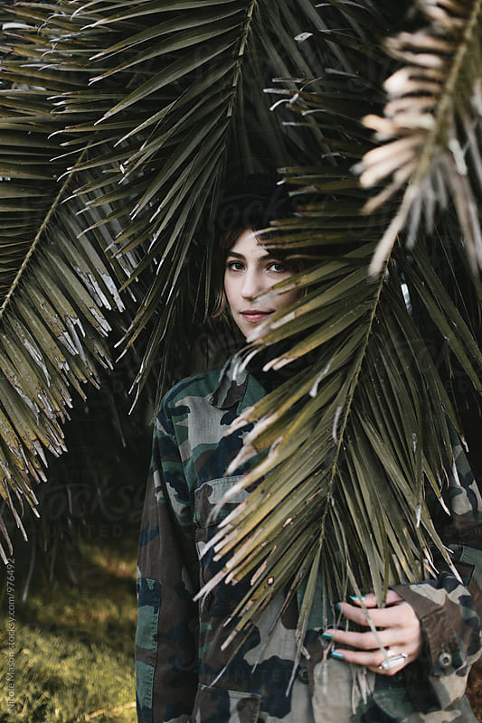 young woman standing in palm tree leaves at sunset by Nicole Mason for Stocksy United