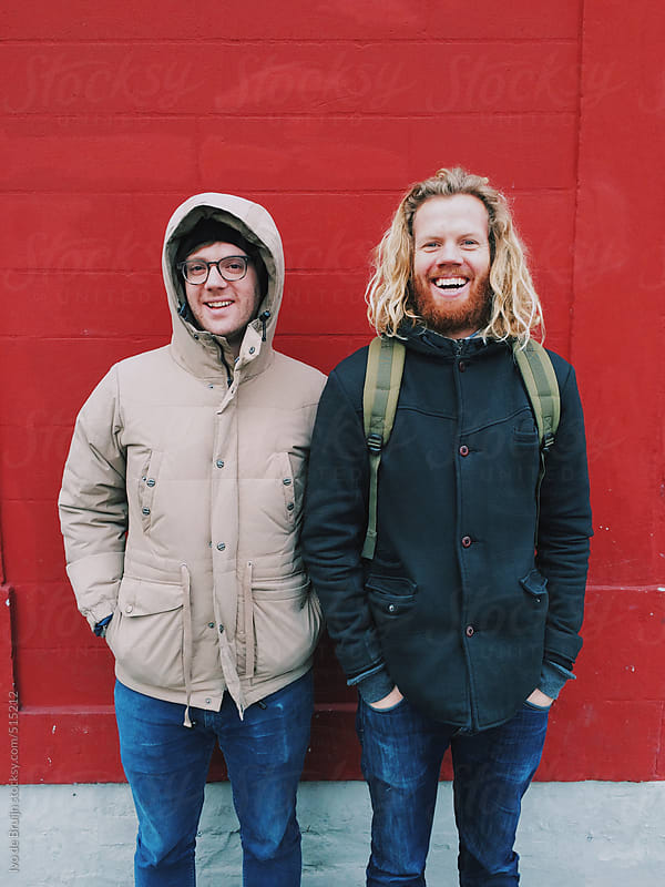 Two good smiling friends in warm jackets standing in front of a red wall by Ivo de Bruijn for Stocksy United