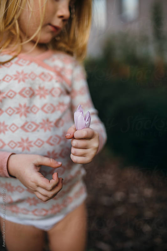 Cut off Profile of a Little Girl Holding a Purple Flower by Amanda Voelker for Stocksy United