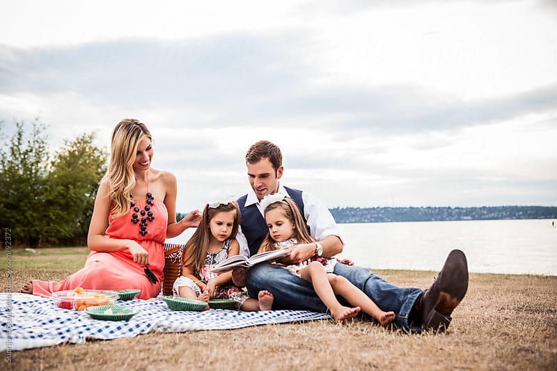 Family having a picnic and reading a book in a park by Suprijono Suharjoto for Stocksy United