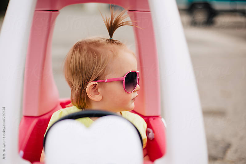 Toddler girl with sunglasses in toy car by Jessica Byrum for Stocksy United