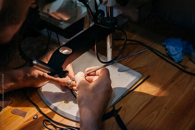 Jeweler repairing a wedding ring with a point welder machine by Gabriel (Gabi) Bucataru for Stocksy United
