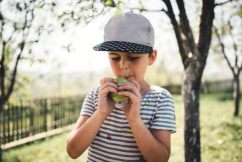 Young boy eating an apple in the yard by Boris Jovanovic for Stocksy United