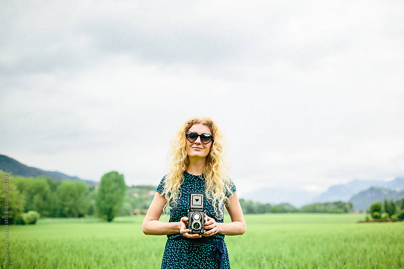 Blonde woman looking at camera holding vintage camera by michela ravasio for Stocksy United