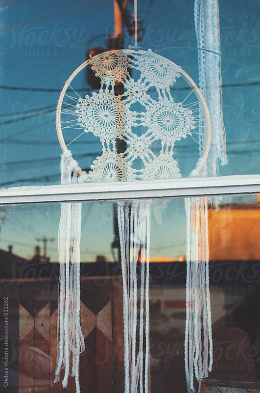 Dreamcatchers through a window of a small town at susnet by Chelsea Victoria for Stocksy United