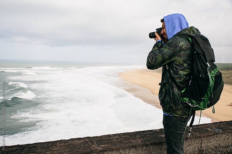 A photographer man taking pictures of the sea breakers from a lookout above by Alejandro Moreno de Carlos for Stocksy United