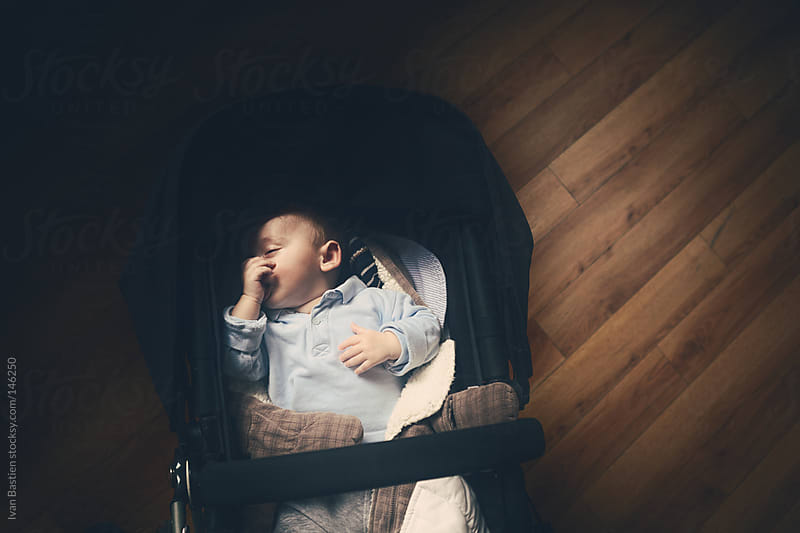 Baby boy falling asleep in a stroller by Ivan Bastien for Stocksy United