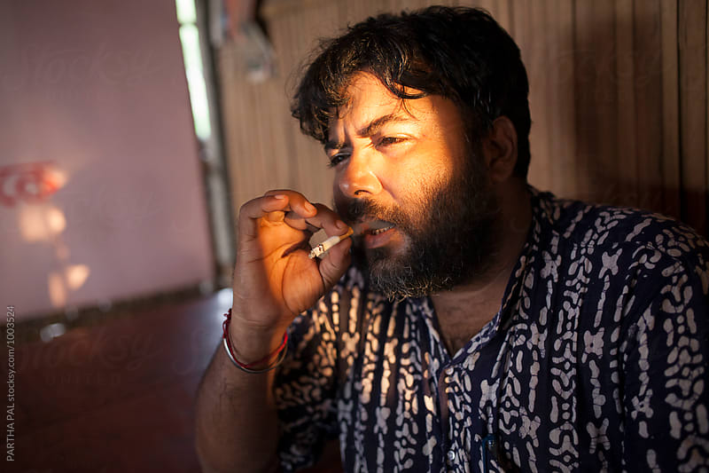 A Man smoking cigarrate by PARTHA PAL for Stocksy United
