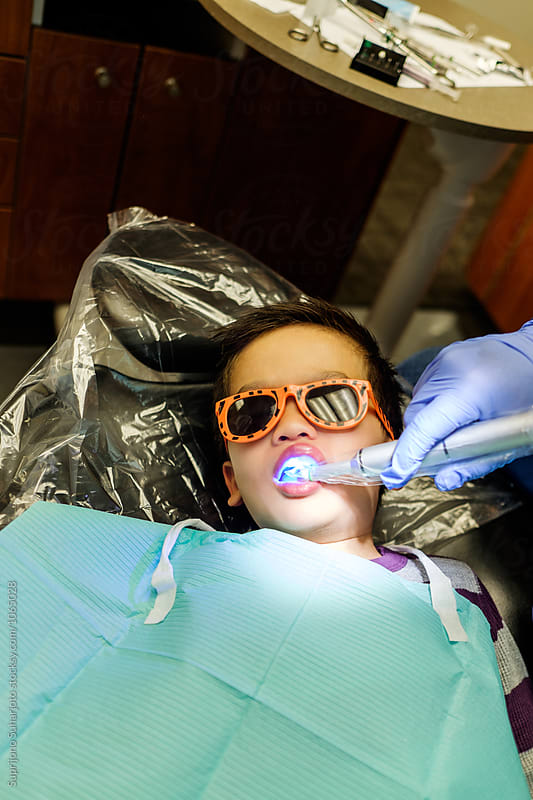 Asian kid getting a filling on his teeth at a dentist office by Suprijono Suharjoto for Stocksy United