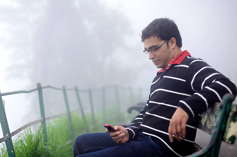 Young man with mobile phone sitting on a wooden bench in a foggy morning by Saptak Ganguly for Stocksy United