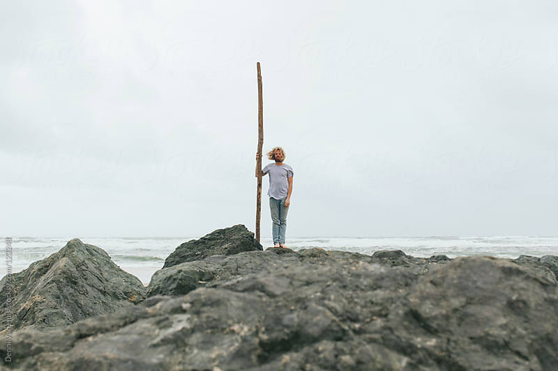 Wild marooned man standing on rocks holding a piece of driftwood by Denni Van Huis for Stocksy United