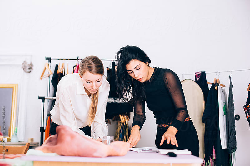 Two young women working on a pattern of dress by michela ravasio for Stocksy United