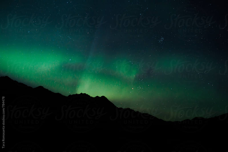 aurora borealis activity over a mountain ridge by Tara Romasanta for Stocksy United