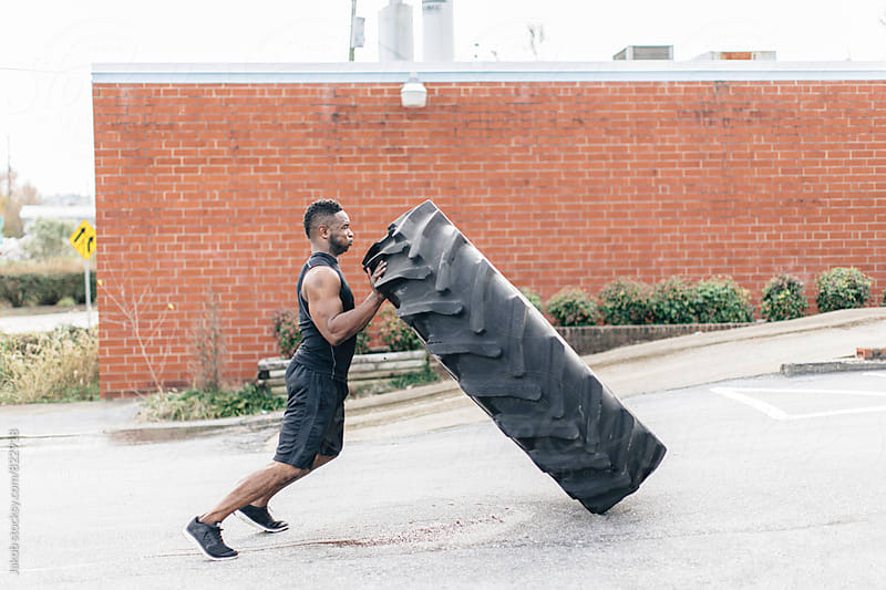 Strong and fit african american athlete flipping a tractor tire by Jakob for Stocksy United
