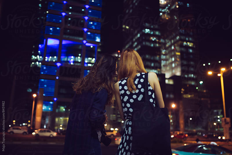 Two friends in the city at night by Maja Topcagic for Stocksy United