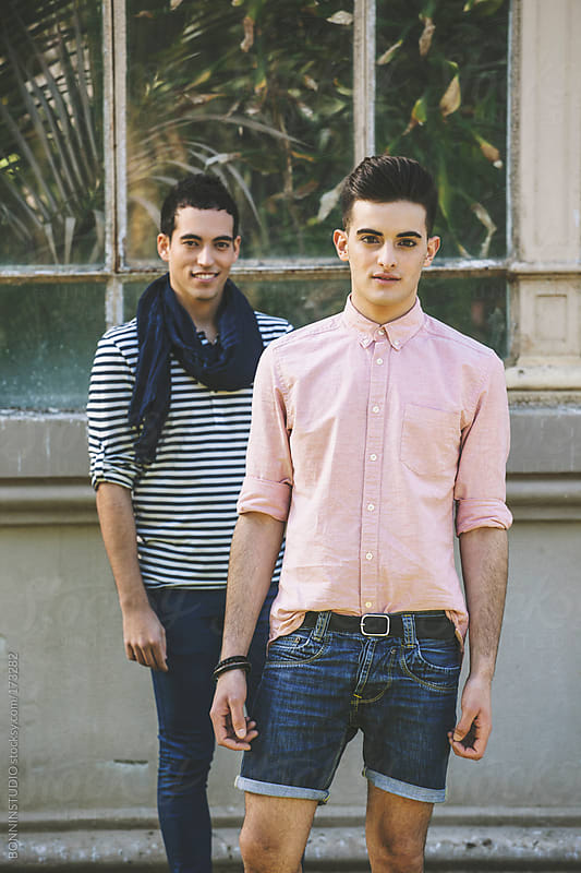 Young gay couple in front a greenhouse looking at camera. by BONNINSTUDIO for Stocksy United
