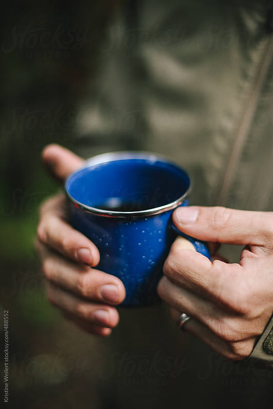 Close up of man holding blue camping mug by Kristine Weilert for Stocksy United