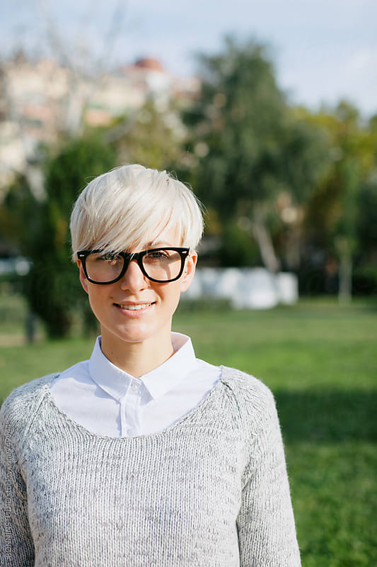 Blonde woman wearing rimmed glasses standing on the park. by BONNINSTUDIO for Stocksy United