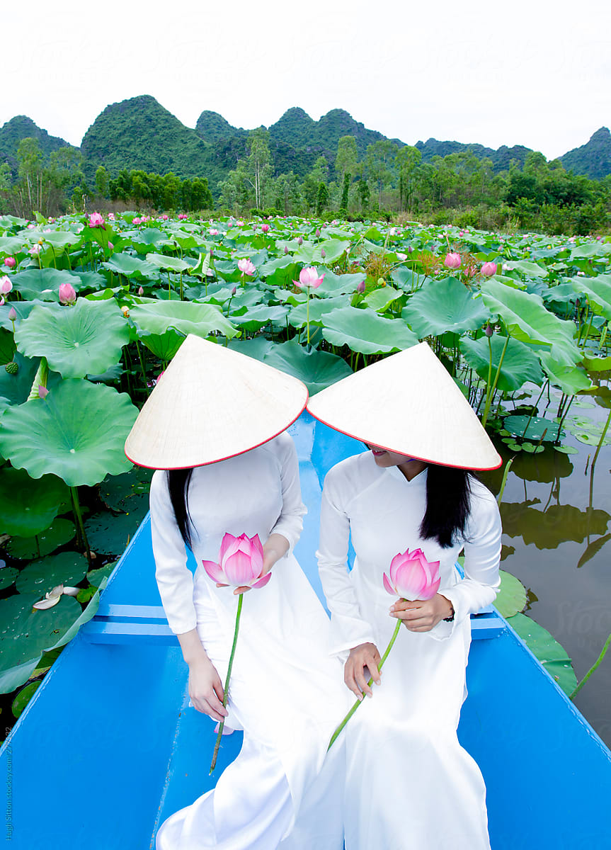 Two Vietnamese Women In Traditional Dress With Lotus Flowers