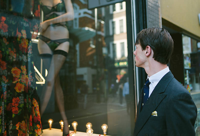 Smartly dressed man looking in a lingerie shop window by kkgas for Stocksy United