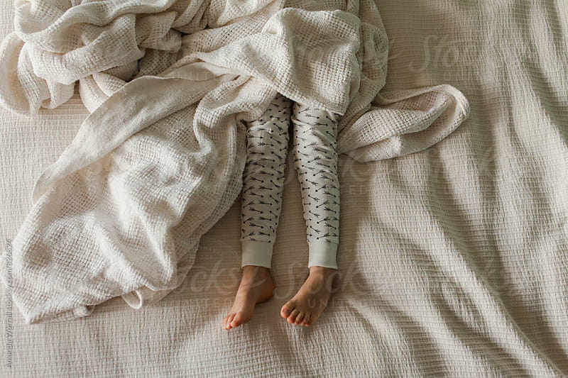 The legs of sleeping girl in bed with arrow print pajamas by Amanda Worrall for Stocksy United