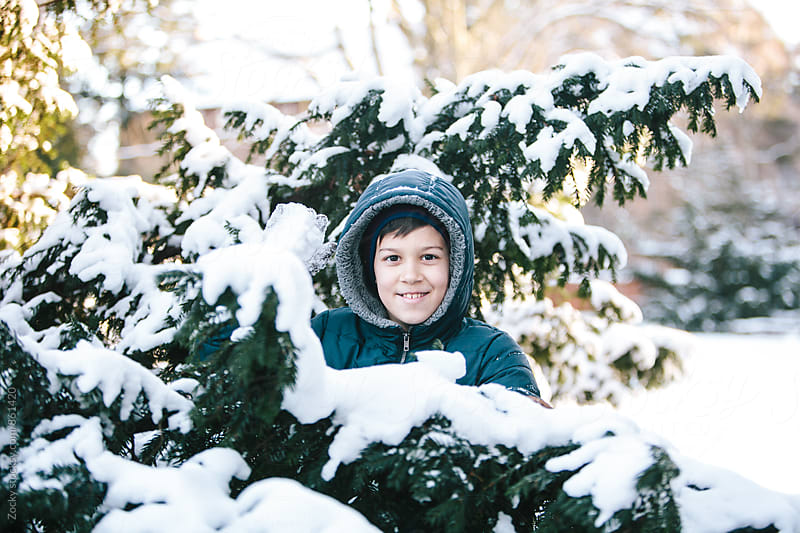 Happy boy in blue winter jacket playing snowballs  by Zocky for Stocksy United