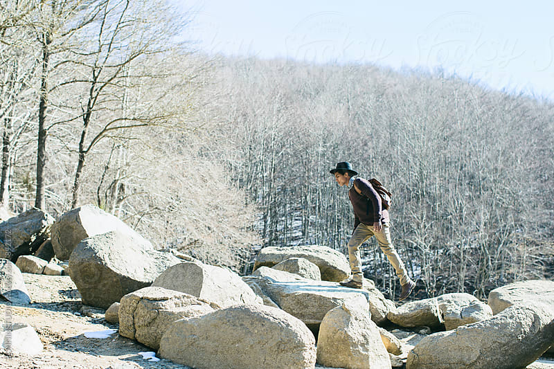 Mountaineer walking on rocks enjoying the nature. by BONNINSTUDIO for Stocksy United