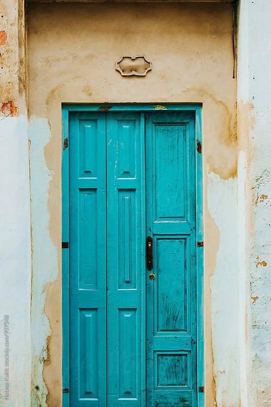 Turquoise door on a yellow wall by Natasa Kukic for Stocksy United