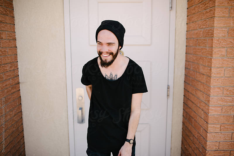 Young man smiles in front of door  by Drew Schrimsher for Stocksy United