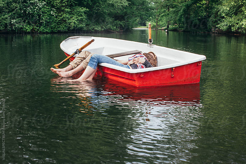 Young Heterosexual Couple Embracing and Napping in Rowboat on Lake by Julien L. Balmer for Stocksy United
