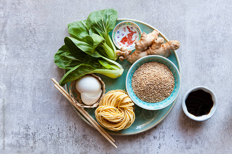 Chinese cuisine cooking ingredients noodles, sesame seeds, soy sauce, ginger root, duck egg and bok choy by Nadine Greeff for Stocksy United