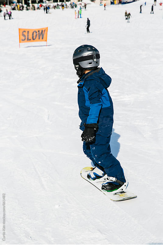 Young boy snowboarding down a hill  by Curtis Kim for Stocksy United
