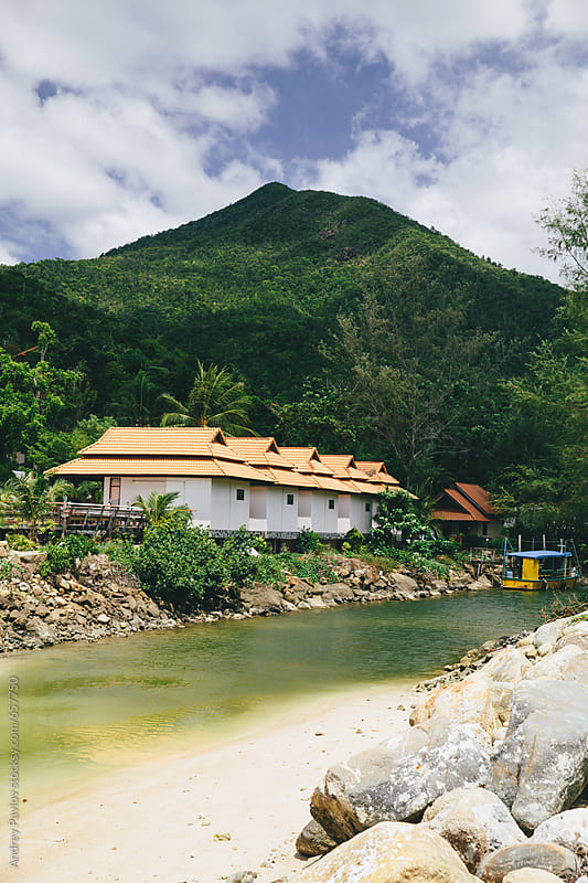 Secluded houses near small tropical river by Andrey Pavlov for Stocksy United