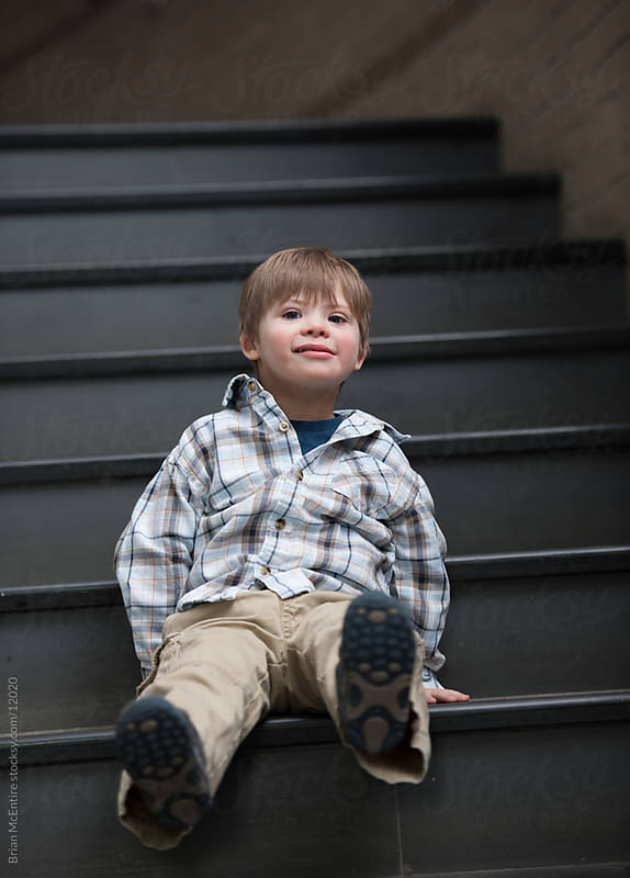 Kindergarten Boy with Down Syndrome Sits on School Stairwell by Brian McEntire for Stocksy United