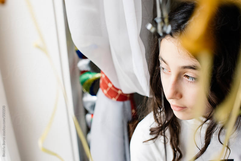 Preteenager girl looking away, staying among party decoration by Beatrix Boros for Stocksy United