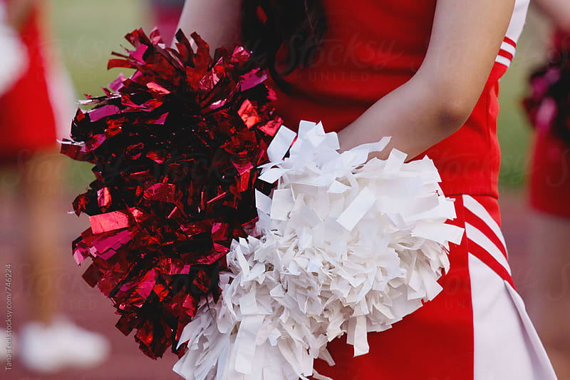 cheerleader holds pom poms at game by Tana Teel for Stocksy United