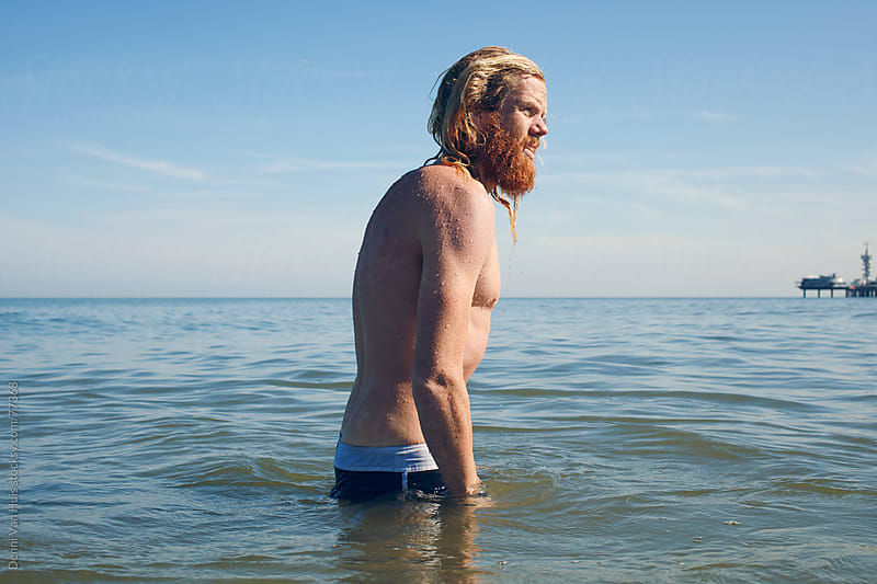 Young healthy man with beard walks out of the ocean by Denni Van Huis for Stocksy United